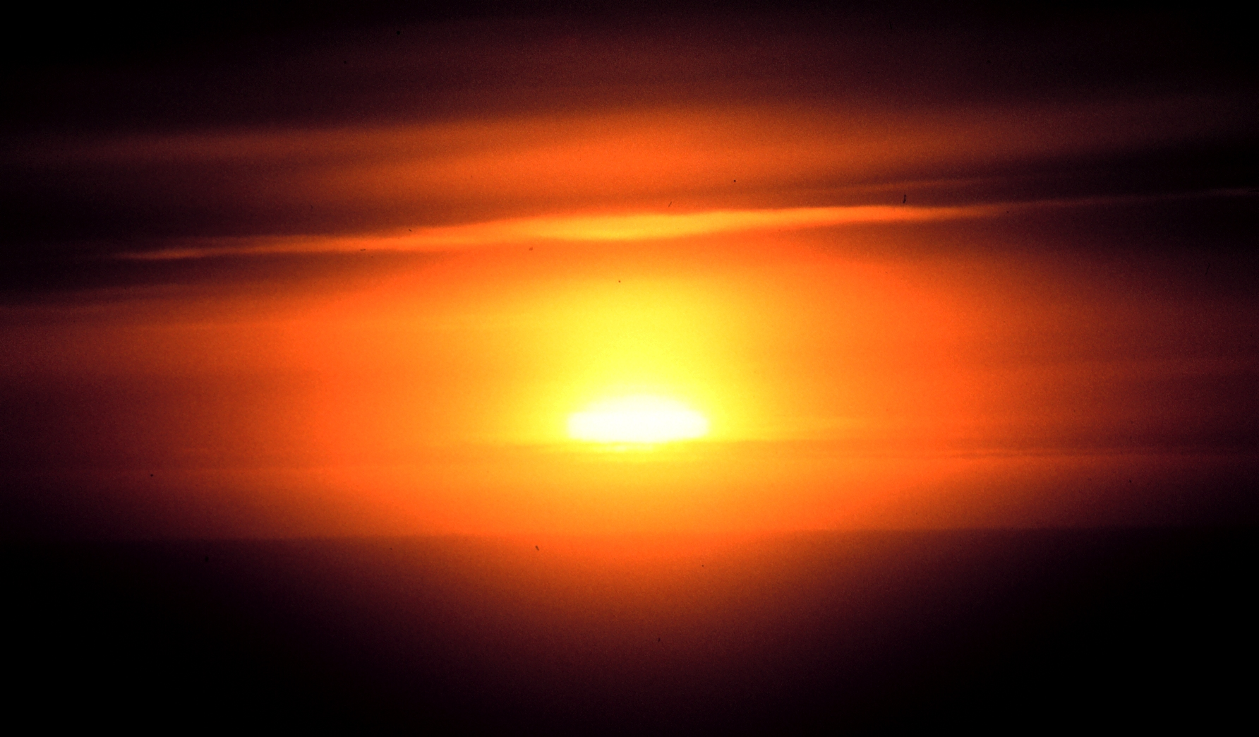 Haze_and_clouds_obscure_the_setting_sun_-_NOAA.jpg